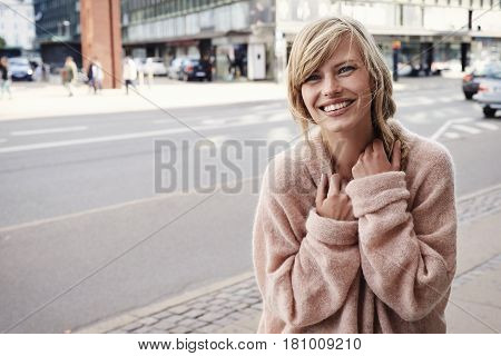 Stunning city girl in sweater smiling at camera