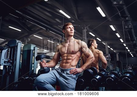 Athlete man with dumbbells in hands on a simulator in the gym.