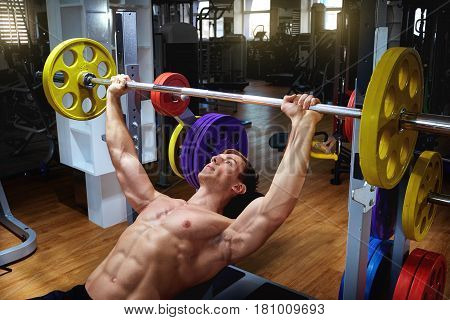 Athlete male doing exercises with a bar lying down in the gym.