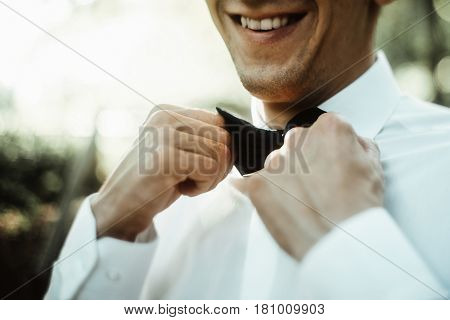 Stylish Elegant Groom Tying Classic Bowtie And Smiling In The Sunny Woods