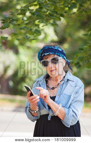 Old woman talking on mobile phone. Senior walking outdoors