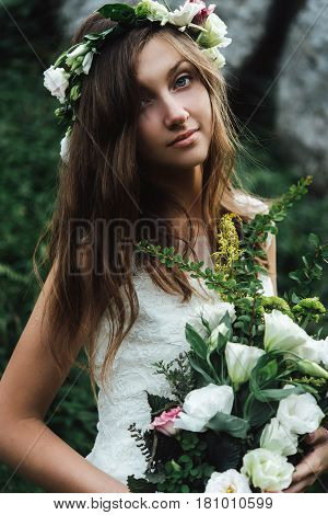 Stylish Sensual Boho Bride With Bouquet On Background Of Rocks And Woods