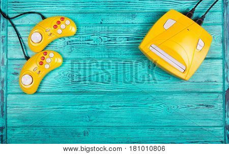 Two yellow joystick and game console on a blue wooden background. Video game console GamePad. Copy space