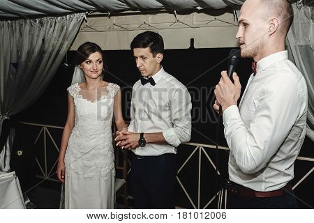 Stylish gorgeous bride and elegant groom with toastmaster at the wedding reception