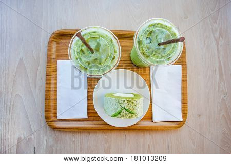 Ice Green Tea And Green Tea Roll Cake On Wooden Table