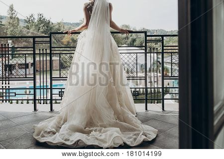 Luxury Bride In Amazing Rich Dress On Her Wedding Day. Stylish Modern Bride In Hotel Room In The Mor