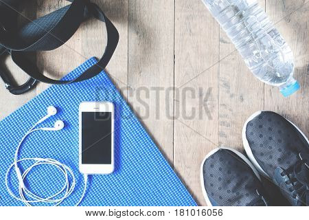 Flat lay of mobile phone with earphones and sport equipments on wood background. Workout and fitness items top view