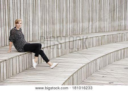 Beautiful woman sitting on wooden step portrait