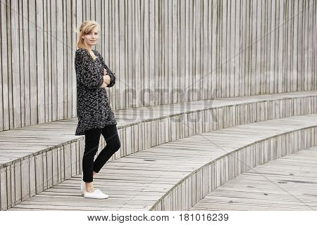 Smiling blond woman standing on wooden step