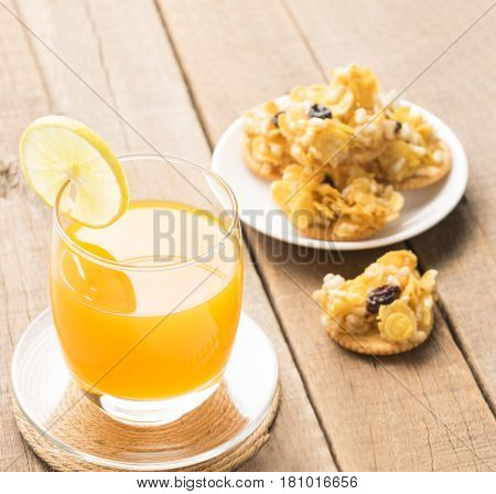 Orange juice and cerealscrackersnack on table wood background