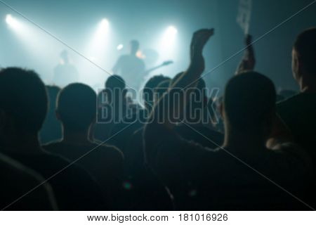 Blur defocused concert crowd fans as abstract background people at popular rock music live performance hands in the air