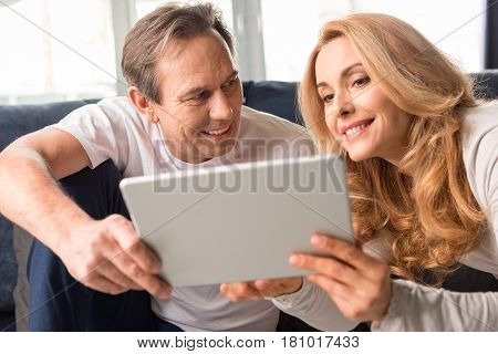 Happy Middle Aged Couple Using Digital Tablet At Home