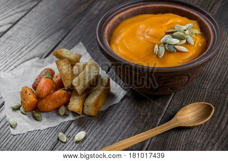 Pumpkin cream soup in a clay bowl with snack fried croutons bread,baked carrots on dark wooden  table