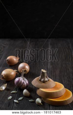 Pumpkin and ingredients for cooking over dark wooden  background.  Fresh pumpkin slice, garlic,onion. Pumpkin cream soup