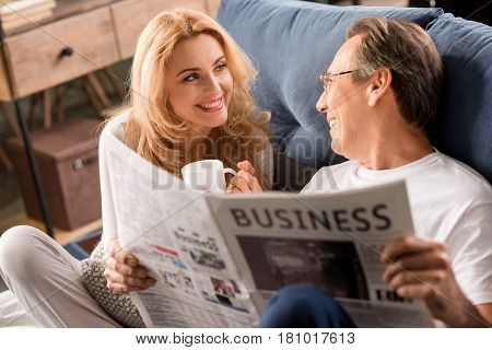 Happy Middle Aged Couple Sitting On Bed, Man Reading Newspaper At Home