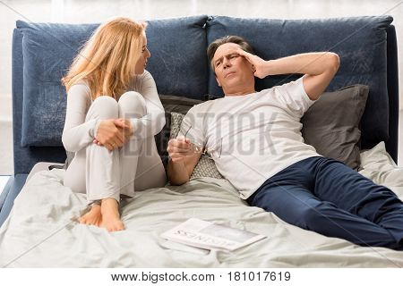 Middle Aged Couple Quarreling And Lying On Bed At Home, Man With Headache