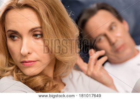 Man Lying In Bed And Touching Hair Of Upset Middle Aged Woman
