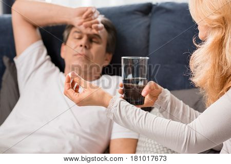 Blonde Woman Holding Glass With Water And Giving Medicine To Sick Man