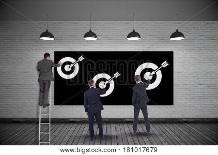 Digital composite of Businessmen setting targets on wall