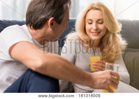 Happy Middle Aged Couple Holding Glasses With Orange Juice On Bed