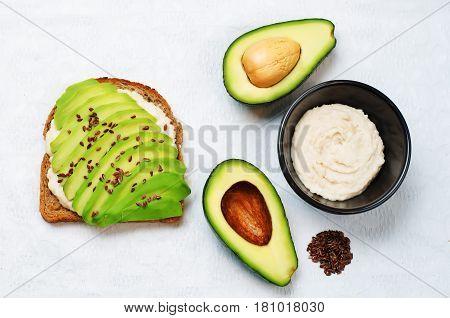 Healthy white bean hummus avocado flax seeds rye breakfast sandwich.