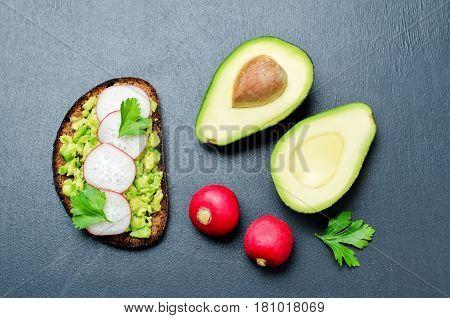Smashed avocado radish parsley rye breakfast sandwich.