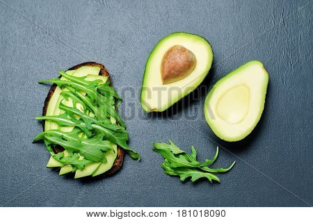 Arugula avocado rye breakfast sandwich on black background