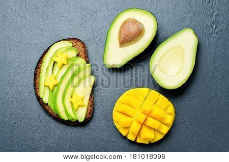 Mango avocado rye breakfast sandwich on black background