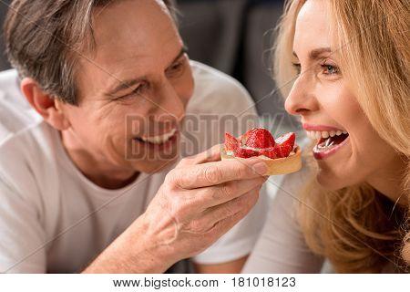 Close-up View Of Smiling Man Feeding Beautiful Blonde Woman At Morning