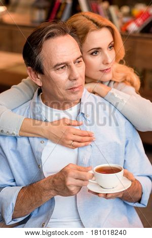 Pensive Mature Couple With Tea Cup Embracing And Looking Away