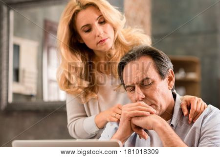 Blonde Middle Aged Woman Looking At Upset Husband Sitting At Home