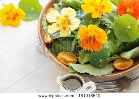 Fresh green salad with edible flowers nasturtium in wooden serving dish