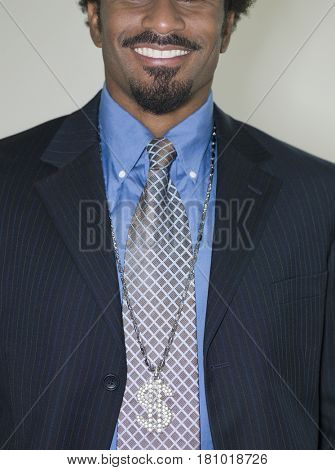 African businessman wearing jeweled dollar sign necklace