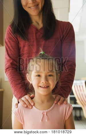 Asian mother with hands on daughter's shoulders