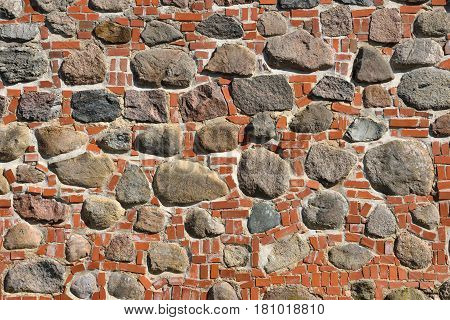 Closeup view of old wall of medieval castle made of red bricks and stone