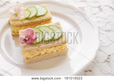 Egg and cucumber afternoon tea sandwiches with edible flowers toning