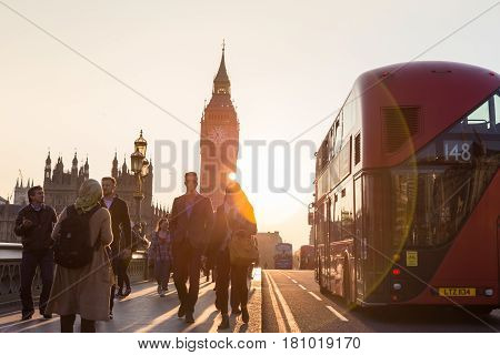 London, UK - April 7, 2015: Traffic and pedestrians passing on Westminster Bridge in sunset on 7th of April, 2017 in London. Big ben and Palace of Westminster aka Houses of Parliament in background.