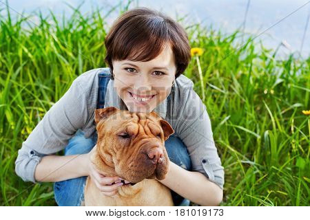Portrait of laughing happy young woman hugging her red cute dog Shar Pei. True friends forever people pets concept.