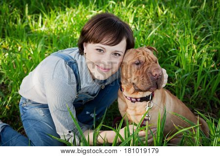 Smiling happy young woman hugging her red cute dog Shar Pei in the green grass in park, true friends forever people concept.