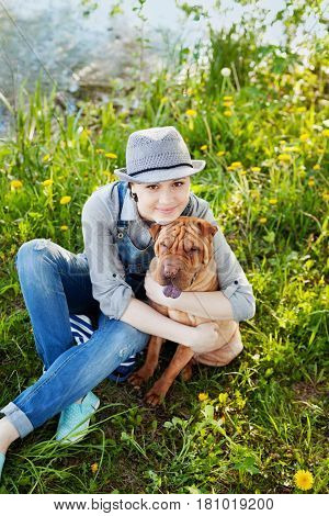 Young woman or girl in denim overalls and hat hugging his beloved dog Shar Pei. True friends forever people pets concept.