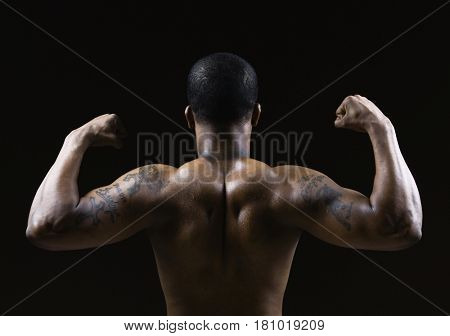 Rear view of African American man flexing