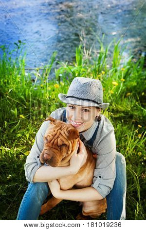 Happy woman in denim overalls and hat with her dog Shar Pei sitting in the meadow near the lake at sunset, true friends forever people pets concept.