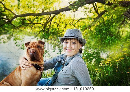 Happy young woman in hat with dog Shar Pei sitting in the field in golden sunset light. True friends forever people with pets concept.