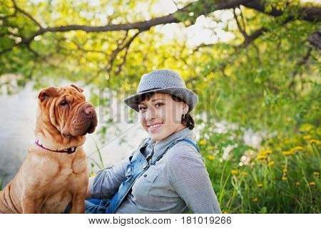 Happy young woman in denim overalls and hat with red cute dog Shar Pei sitting in the field near the lake at sunset.