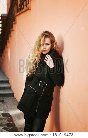 Pretty young fashion woman with long curly hair looking into the distance and posing outdoor near the wall in the street background. Sensual look, warm toned.