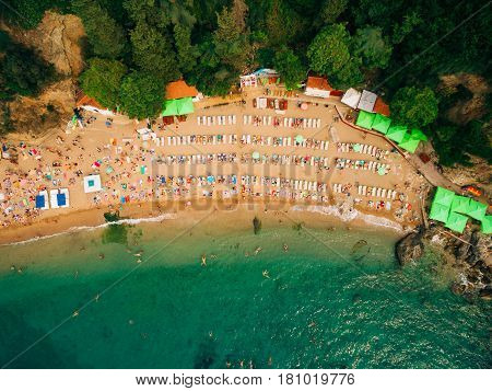 Top View of Beach. Aerial view of sandy beach with tourists swimming in beautiful clear sea water. People on the beach.