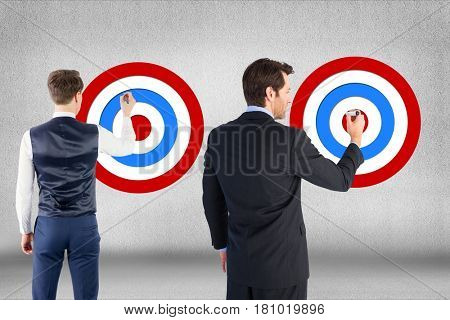 Digital composite of Rear view of businessmen setting targets on wall