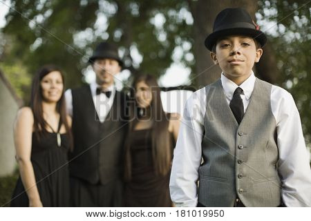 Hispanic boy in suit with family in background