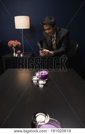Asian man dialing cell phone