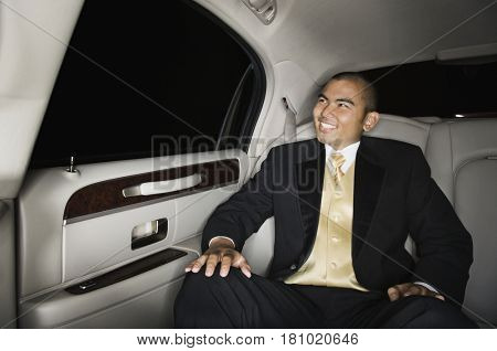Asian man wearing suit in limousine